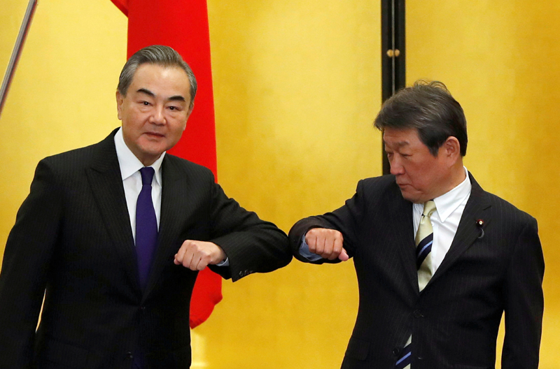 China's State Councilor and Foreign Minister Wang Yi (L) and his Japanese counterpart Toshimitsu Motegi bump elbows at the start of their talks, amid the coronavirus disease (COVID-19) outbreak, in Tokyo, Japan, November 24, 2020. Photo: Reuters
