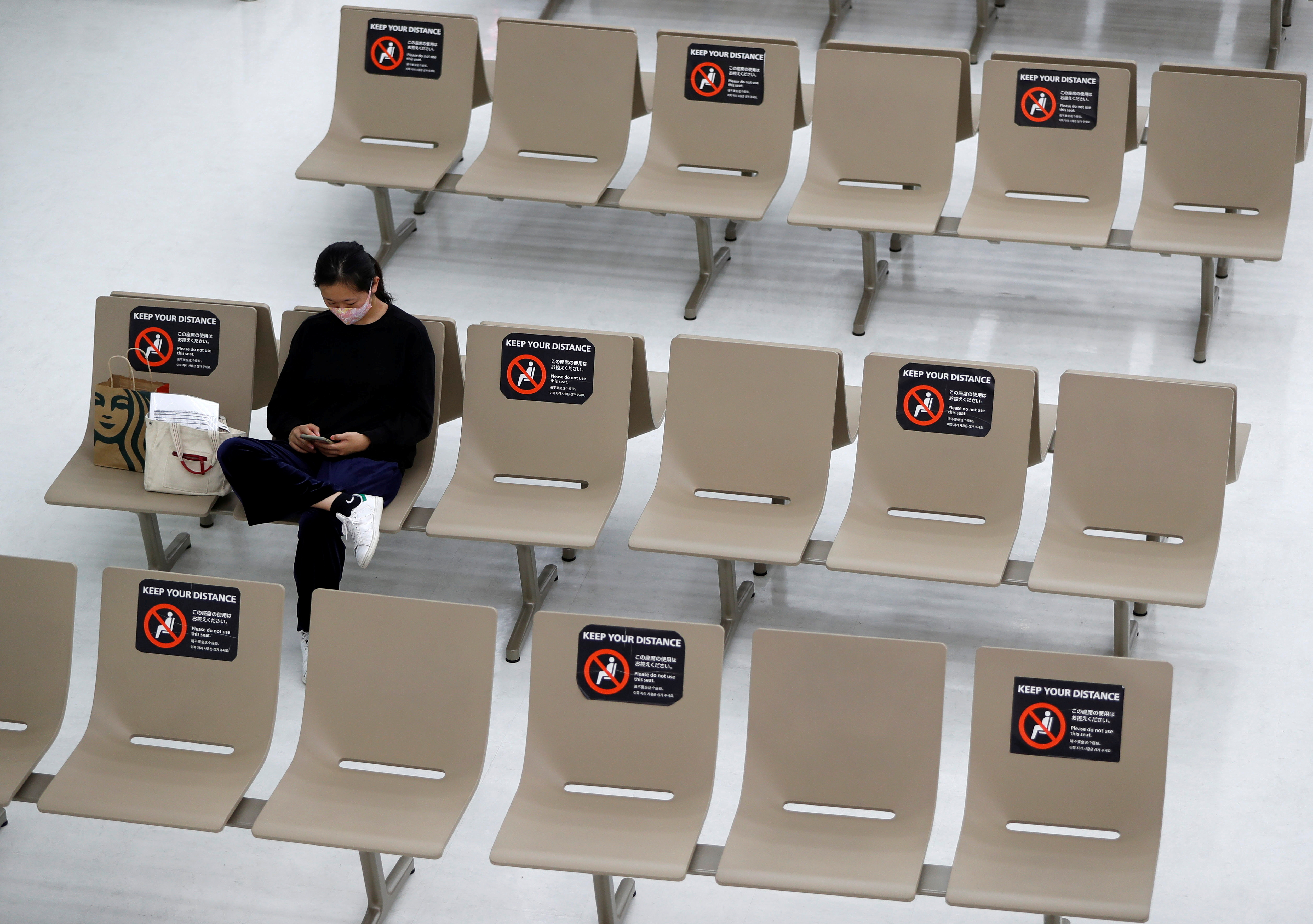 Signs for social distancing are seen on seats at the arrival zone of Narita International Airport, where there are fewer passengers than usual amid the coronavirus disease (COVID-19) outbreak, in Narita, east of Tokyo, Japan November 2, 2020. Photo: Reuters