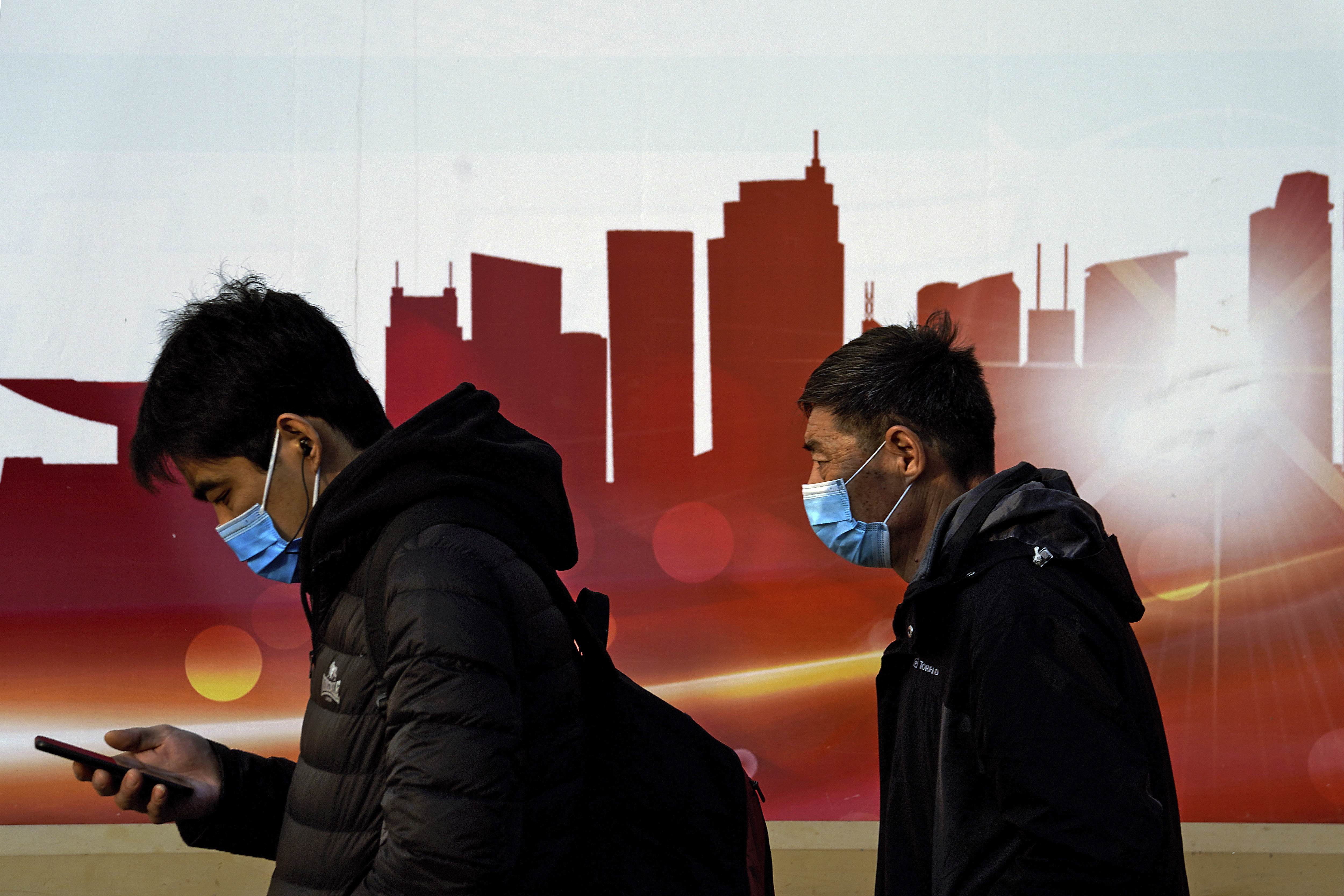 People wearing face masks to help curb the spread of the coronavirus walk by a moral depicting China's skyscrapers along a street in Beijing, Sunday, Dec. 6, 2020. Provincial governments across China are placing orders for experimental, domestically made coronavirus vaccines, though health officials have yet to say how well they work or how they may reach the country's 1.4 billion people. Photo: AP
