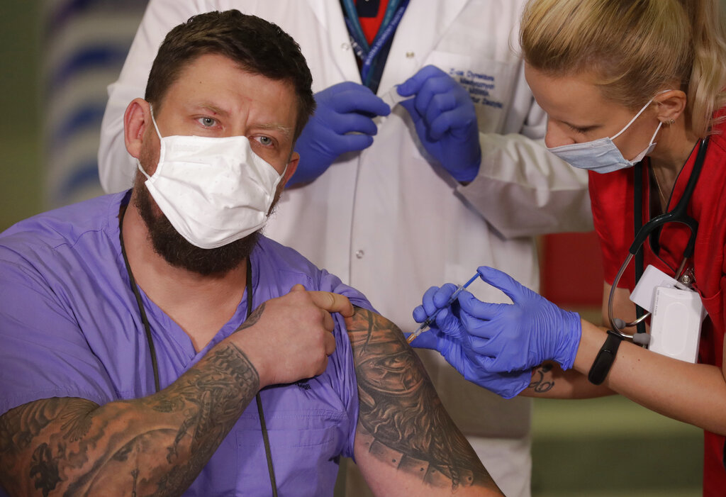 Slawomir Butkiewicz, left, the paramedic of the Interior Ministry hospital in Warsaw, the capital's main COVID-19 hospital, is getting the coronavirus vaccination in Warsaw, Poland, Sunday December 27, 2020. Photo: AP