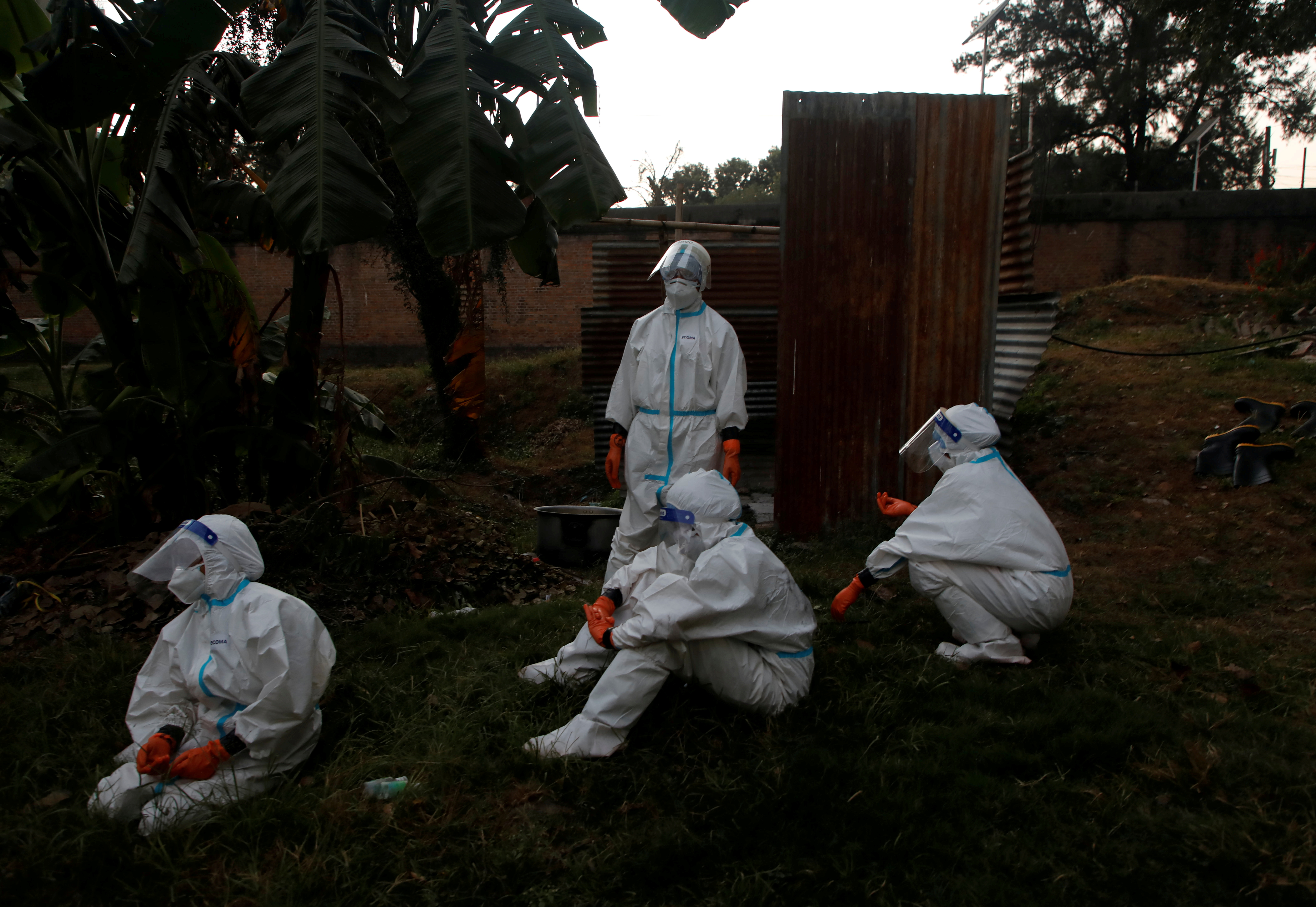 Female soldiers wearing personal protective equipment (PPE) take rest after handling bodies of coronavirus victims, amidst the spread of the coronavirus disease (COVID-19), in Kathmandu, Nepal November 11, 2020. Photo: Reuters