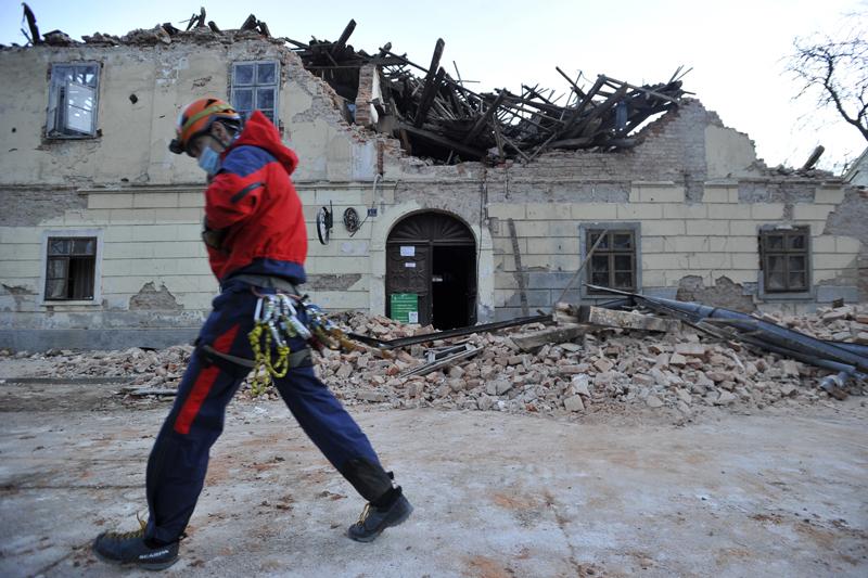 A rescuer walks past a building damaged in an earthquake in Petrinja, Croatia, Tuesday, Dec. 29, 2020. Photo: AP