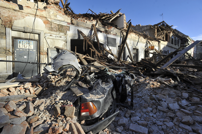 A view of remains of a car covered by debris and buildings damaged in an earthquake in Petrinja, Croatia, Tuesday, Dec. 29, 2020. Photo: AP