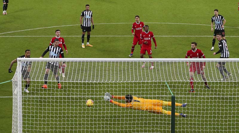 Liverpool's goalkeeper Alisson dives full length to make a save from a header by -Newcastle's Ciaran Clark, at right, during the English Premier League soccer match between Newcastle United and Liverpool at St James' Park stadium in Newcastle, England, on Wednesday, December 30, 2020. Photo: AP