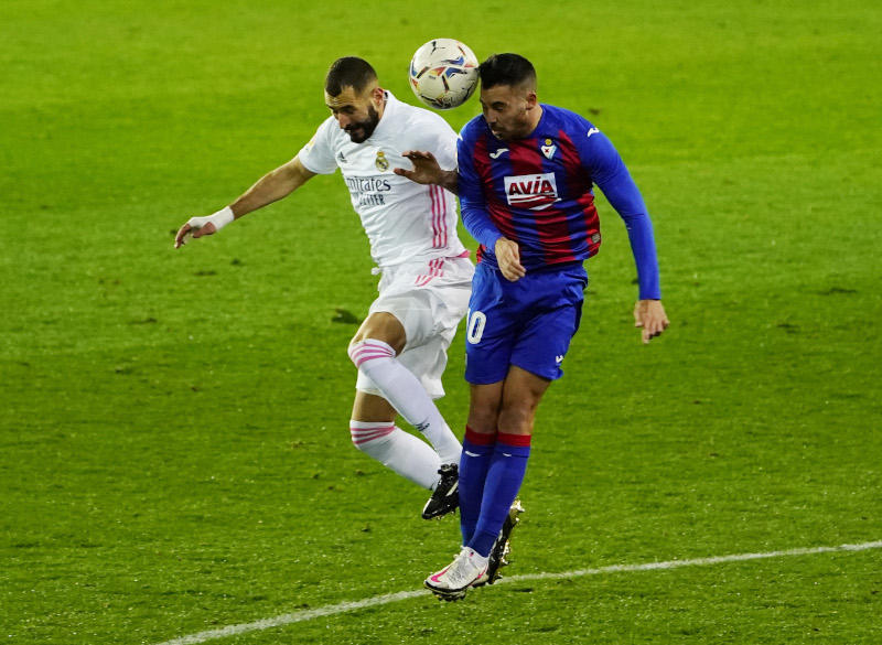 Real Madrid's Karim Benzema in action with Eibar's Edu Exposito  during the La Liga Santander match between Eibar and Real Madrid, at Ipurua Municipal Stadium, in Eibar, Spain, on December 20, 2020. Photo: Reuters