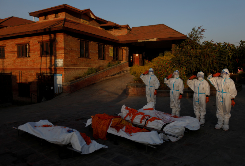 Female soldiers wearing personal protective equipment (PPE) pay tribute to the bodies of coronavirus victims at a crematorium, amidst the spread of the coronavirus disease (COVID-19), in Kathmandu, Nepal November 11, 2020. Picture taken November 11, 2020.  Photo: Reuters