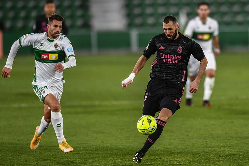 Real Madrid's Karim Benzema, right, controls the ball in front of Elche's Josema during the Spanish La Liga soccer match between Real Madrid and Elche CF at the Manuel Martinez Valero stadium in Elche, Spain, Wednesday, December 30, 2020. (AP Photo/Jose Breton)