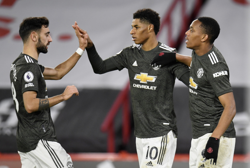 Manchester United's Marcus Rashford celebrates scoring their third goal with Bruno Fernandes and Anthony Martial during the Premier League match between Sheffield United and Manchester United, at Bramall Lane, n in Sheffield, Britain, on December 17, 2020. Photo: Pool via Reuters