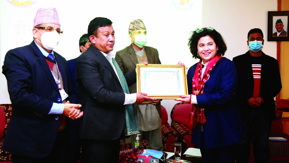 Minister Parbat Gurung (centre) honouring an employee for her long tenure at Radio Nepal, in Kathmandu, on Tuesday. Photo: RSS