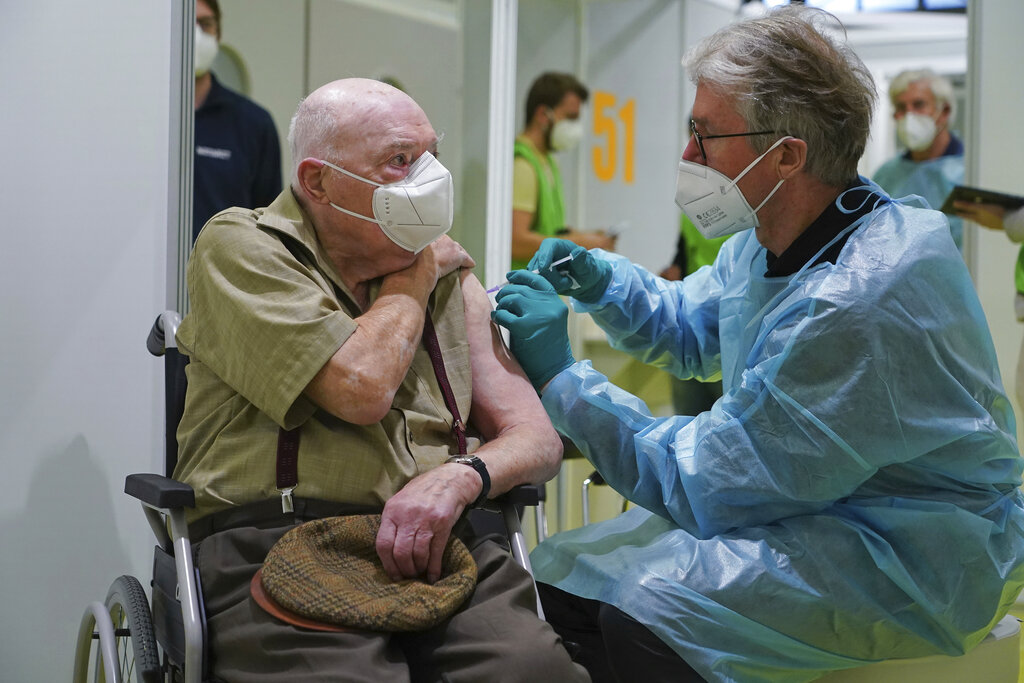 A doctor inoculates Herri Rehfeld, 92, against the new coronavirus with the Pfizer/BioNTech vaccine at the vaccination center at the Messe Berlin trade fair grounds on the center's opening day in Berlin, Germany, Monday, Jan. 18, 2021. The center is the third to open in Berlin. Three more are to open in coming weeks once shipments of the Pfizer/BioNTech and Moderna vaccines pick up pace. Photo:AP