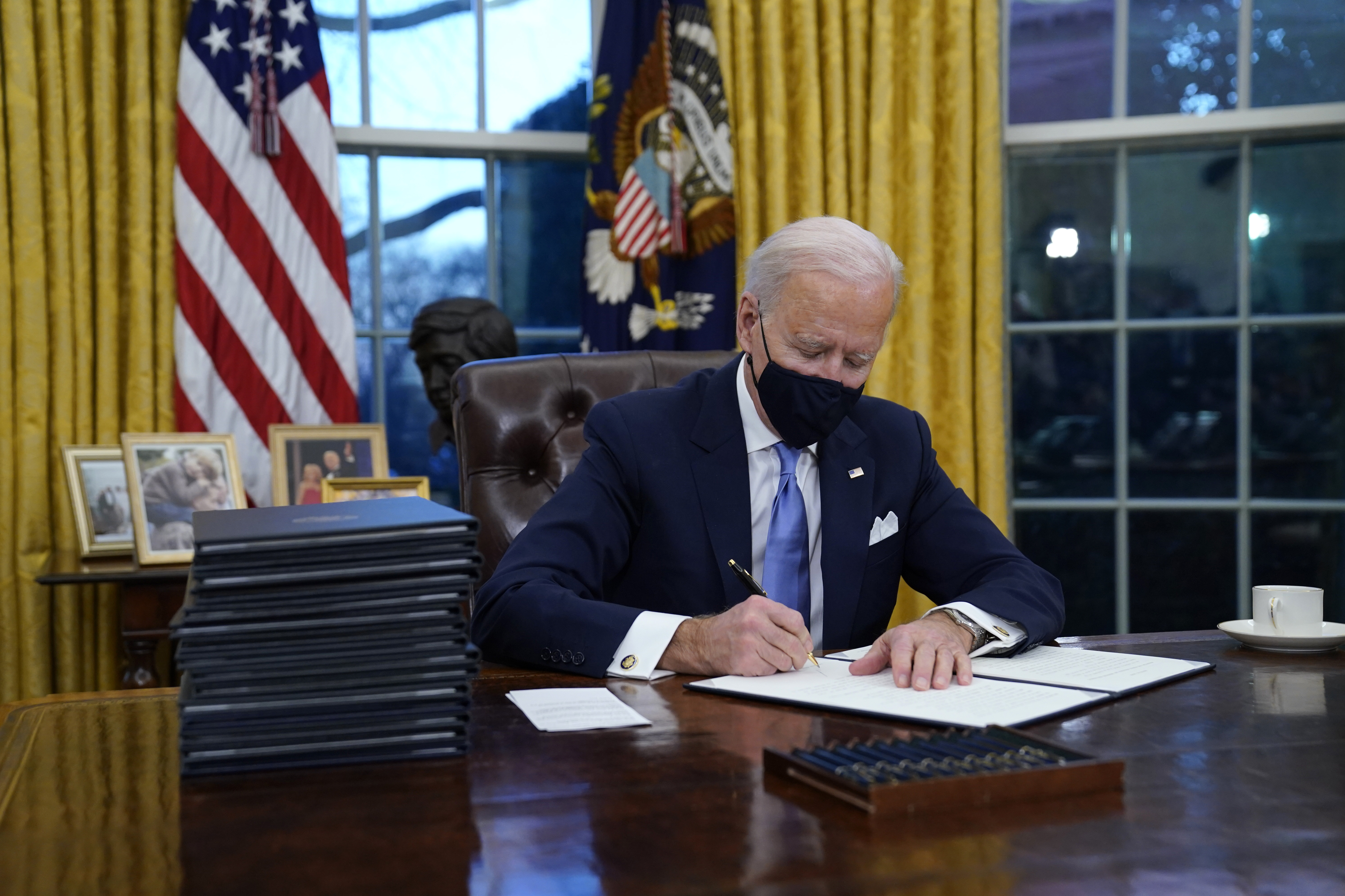 President Joe Biden signs his first executive order in the Oval Office of the White House on Wednesday, Jan. 20, 2021, in Washington.u00a0Photo: AP