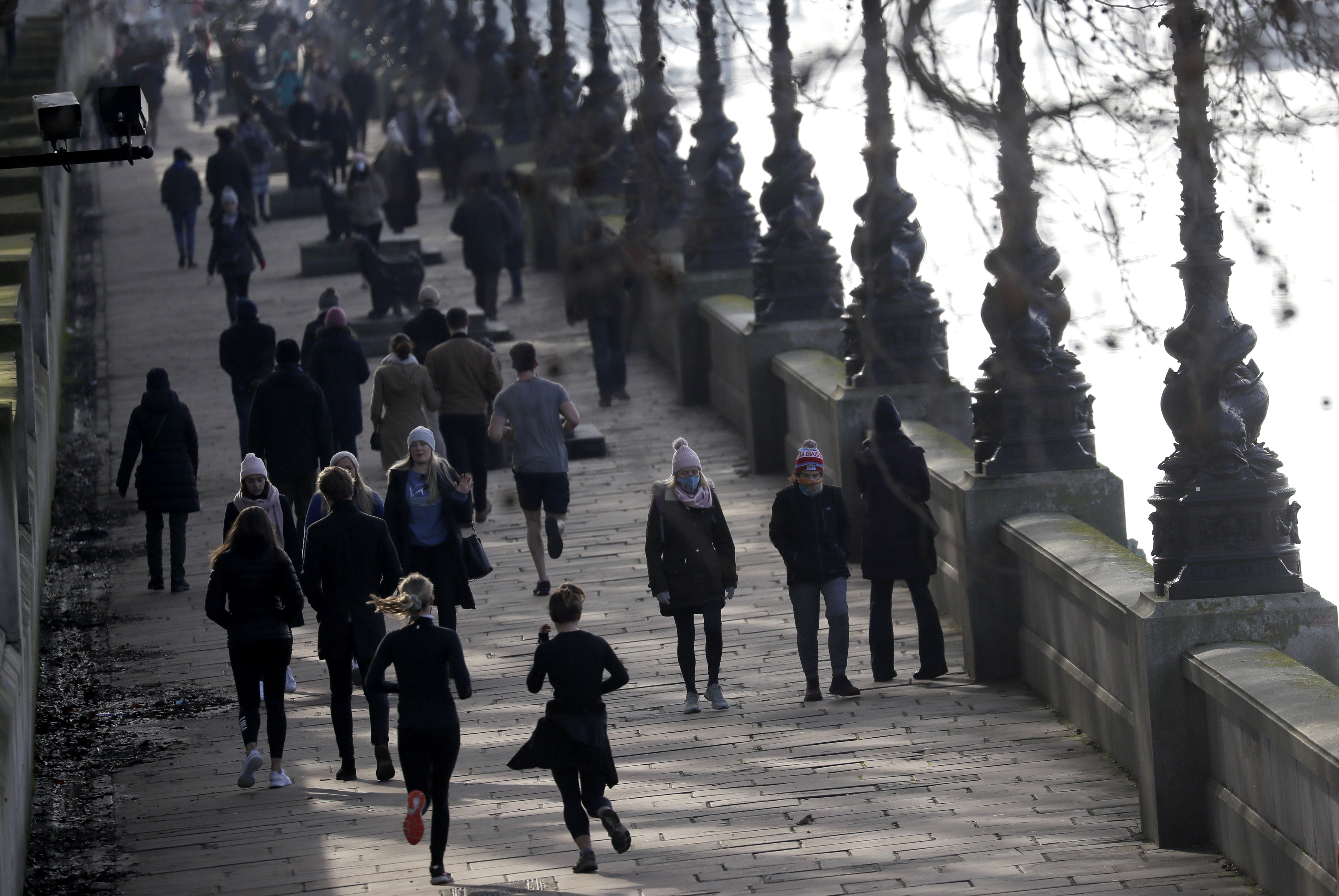 People exercise along the bank of the River Thames in London, Saturday, Jan. 23, 2021 during England's third national lockdown since the coronavirus outbreak began. The UK is under an indefinite national lockdown to curb the spread of the new variant, with nonessential shops, gyms and hairdressers closed, and people being told to stay at home. Photo: AP