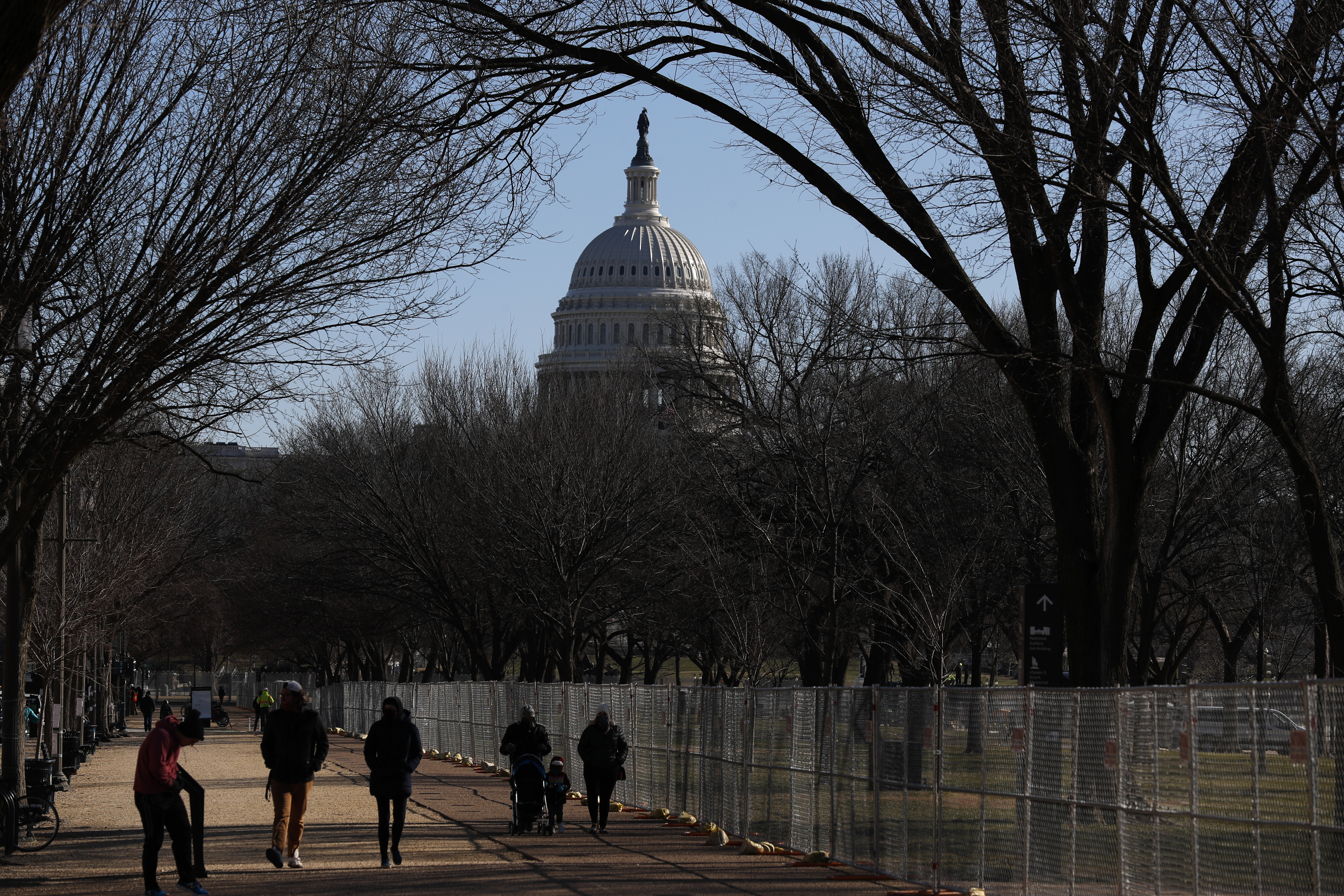 People stroll past a section of the National Mall by the Capitol where workers were still dismantling inauguration installations, after most downtown streets and public spaces had reopened to the public, on Saturday, Jan. 23, 2021 in Washington. Biden is looking to jump-start his first 100 days in office with action and symbolism to reassure a divided and weary public that help is in the offing. Photo: AP