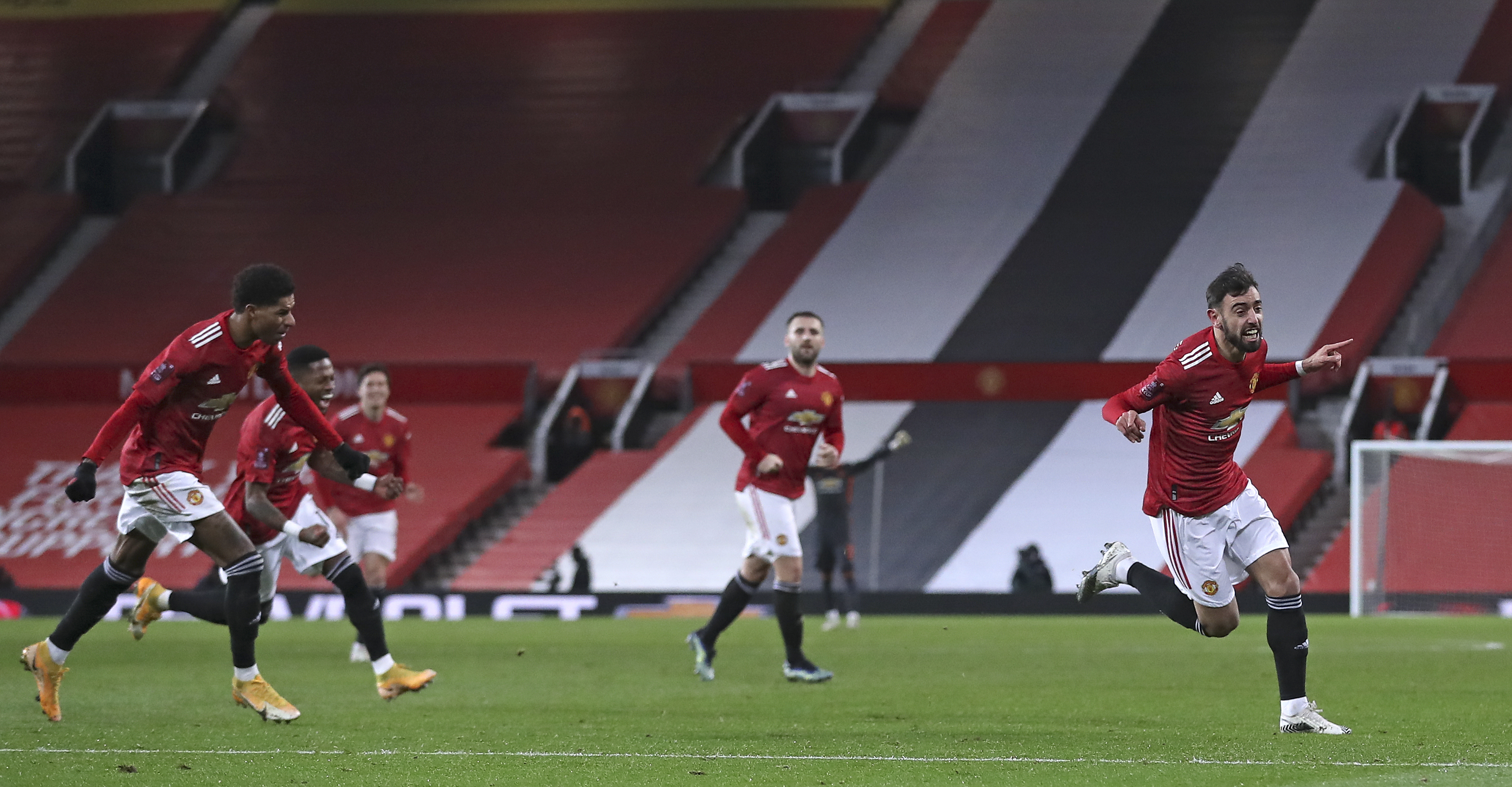 Manchester United's Bruno Fernandes, right, celebrates scoring his side's third goal during the English FA Cup 4th round soccer match between Manchester United and Liverpool at Old Trafford in Manchester, England, Sunday, Jan. 24, 2021. Photo:  AP