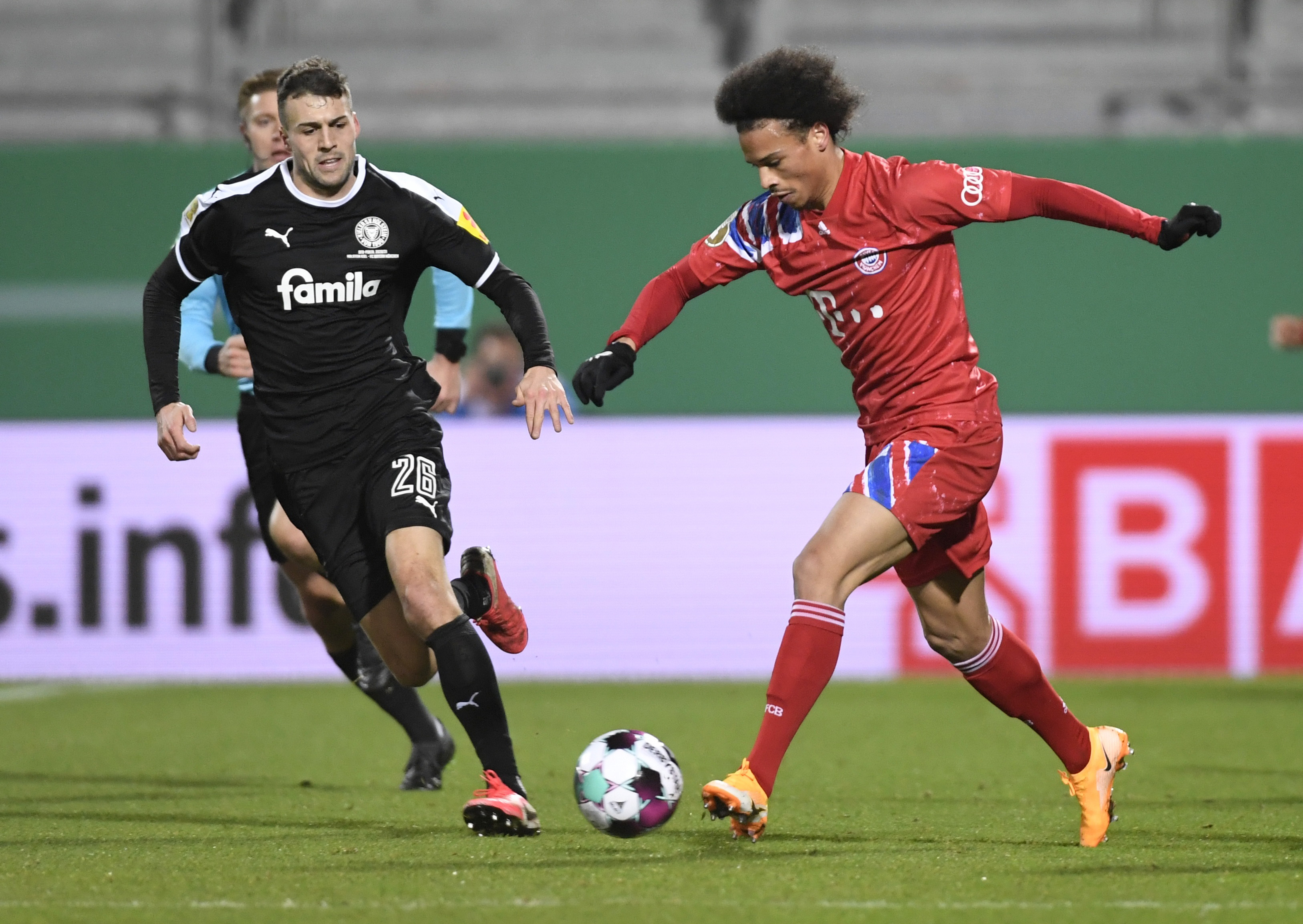 Holstein Kiel's Jonas Meffert in action with Bayern Munich's Leroy Sane. Photo: Reuters