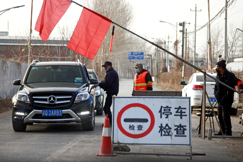 Volunteers stop a car at a checkpoint on a road leading into their village, following the coronavirus disease (COVID-19) outbreak, on the outskirts of Beijing near the provincial border with Hebei province, China January 12, 2021. Photo: Reuters