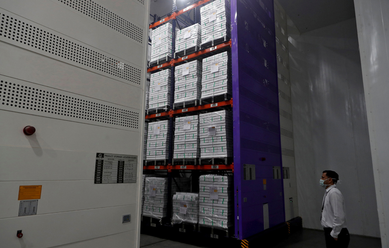 A man wearing a protective mask stands next to boxes containing the vials of AstraZeneca's  COVISHIELD, coronavirus disease (COVID-19) vaccine, inside a cold room at the Serum Institute of India, Pune, India, 30 November 2020. Photo: Reuters/File