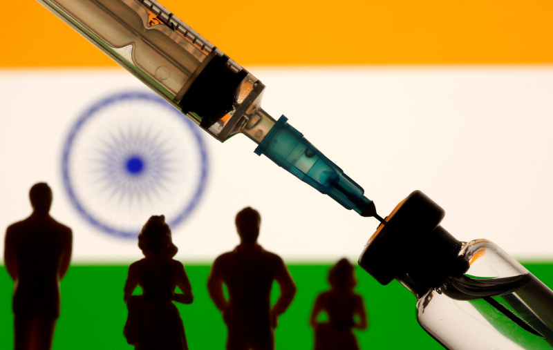 A vial, sryinge and small toy figures are seen in front of a displayed India flag in this illustration taken January 11, 2021. Photo: Reuters