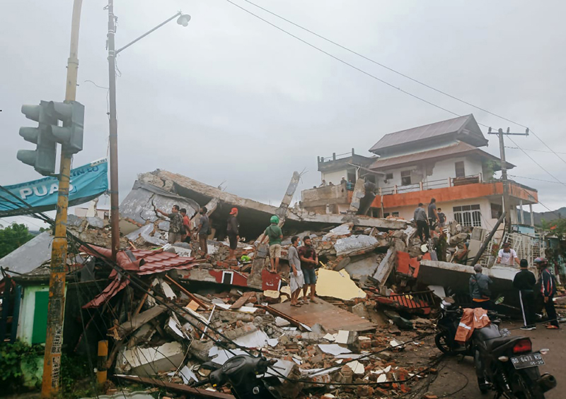 Residents inspect earthquake-damaged buildings in Mamuju, West Sulawesi, Indonesia, Friday, Jan. 15, 2021. Photo: AP