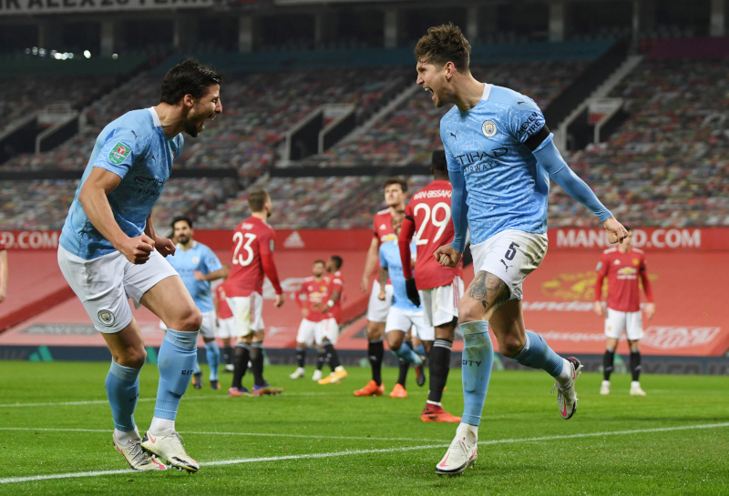 Manchester City's John Stones celebrates scoring their first goal with teammates during the Carabao Cup Semi Final match between Manchester United and Manchester City, at Old Trafford, in Manchester, Britain, on January 6, 2021. Photo: Pool via Reuters