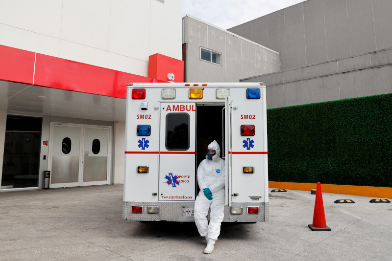 FILE PHOTO: Paramedic Daniel Reyes waits outside the hospital with a 63-year-old patient, who suffers from the coronavirus disease (COVID-19) and is inside the ambulance while waiting for a free bed, as hospitals are fully occupied during the continued outbreak of the coronavirus disease (COVID-19) in Mexico City, Mexico January 13, 2021.  Photo: Reuters