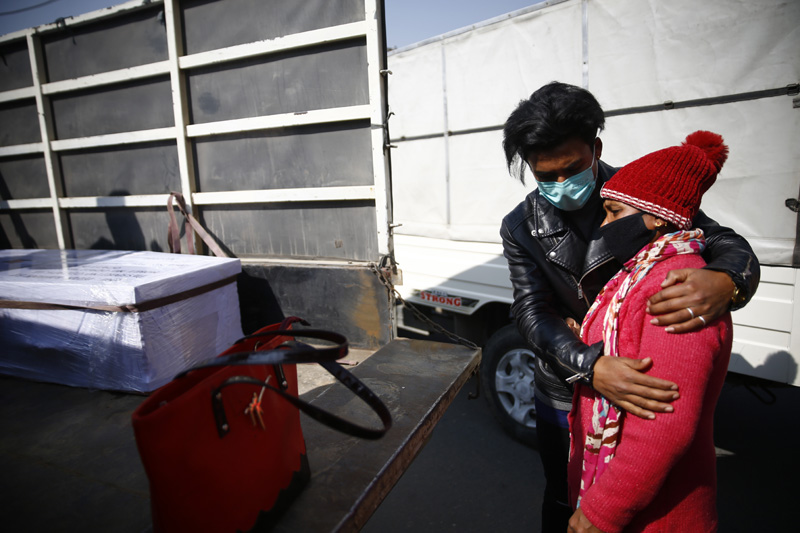 A family member mourns next to a coffin of a Nepalese migrant worker put on a vehicle at Tribhuvan International Airport in Kathmandu, Nepal on Saturday, January 23, 2021.  A total of 17 stranded dead bodies of Nepalese migrant workers were stuck in Malaysia due to the COVID-19 pandemic and lockdowns. The workers died of various illnesses in Malaysia. Photo: Skanda Gautam/THT