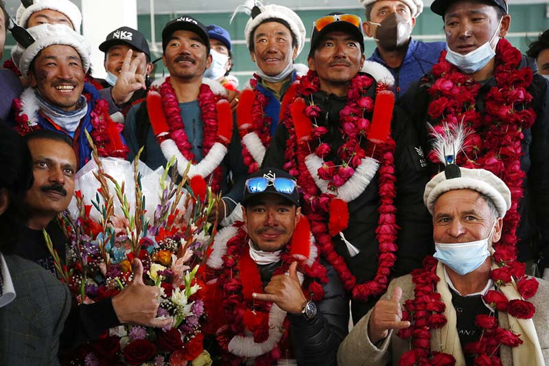 Nepali climber Nirmal Purja (centre) with glasses, and team members, who recently made history by scaling the K2 summit in the winter season, pose for photograph with local tour operators upon their arrival at airport in Islamabad, Pakistan, on Thursday, January 21, 2021. Photo: AP