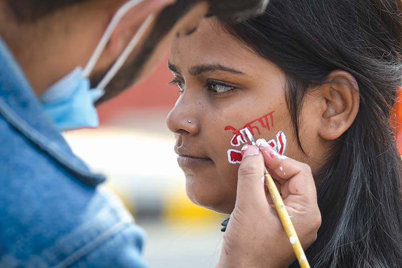 A girl getting her face painted during the protest organised by Nepal Communist Party (NCP) (Dahal-Nepal faction) against the dissolution of the House of Representatives, in Kathmandu, on Friday, January 23, 2021. Photo: Naresh Shrestha/THT