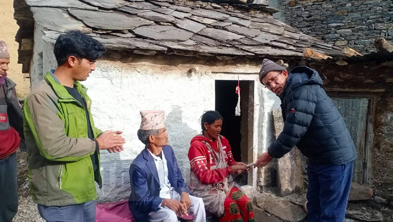 Mayor Padam Baduwal of Badimalika Municipality provides grant amount collected from various supporters to Rati Thapa and his sister. Photo: Prakash Singh/THT